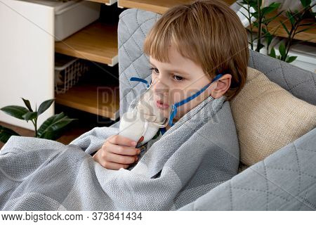 Little Caucasian Boy Making Inhalation With Nebulizer At Home. Child Holds A Mask Vapor Inhaler. Tre