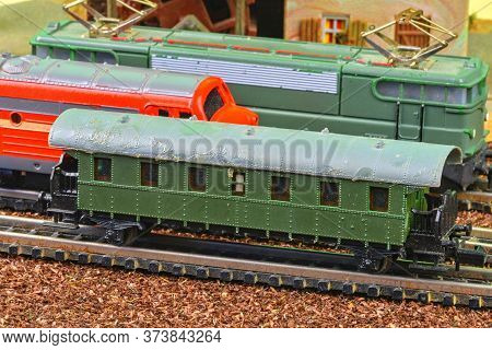 Close-up Of Model Railway Carriage On The Rail Tracks. Perfect Model Of The Electric Locomotive And