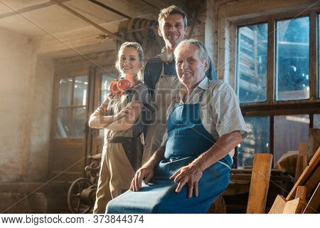 Generations of carpenters in their family business workshop looking at the camera