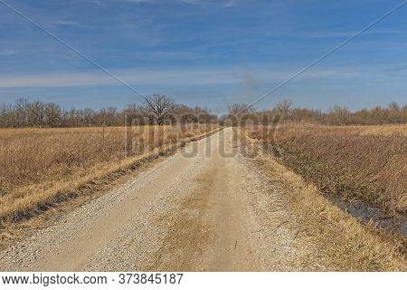 Rural Road Through A Prairie Wetland In The Midewin National Tallgrass Prairie In Illinois