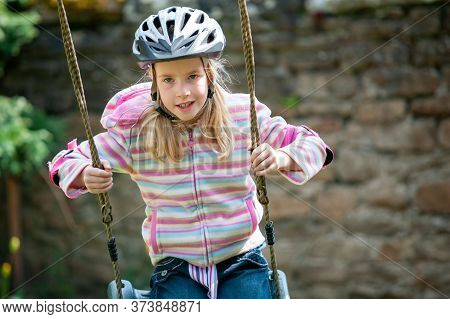 A Young Blonde Girl Wearing A Cycle Helmet While Swinging On A Garden Swing.