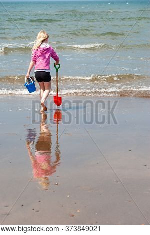 A Young Girl Carries A Bucket And Spade To The Shoreline On A Beach. Her Reflection Is Visible In Th