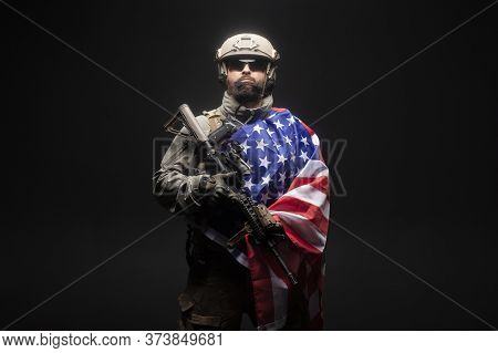 Army Of America. A Soldier In Military Equipment With A Gun Holds The Usa Flag On A Dark Black Backg