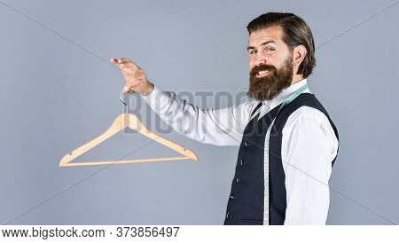 Portrait Of Man Holding Hanger. Tailor Man Use Tape Measure. Professional Male Sartor With Measuring