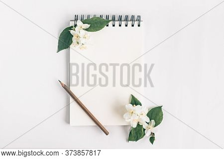 Notepad With Pencil And Rose Flowers Top View On White Background. Messege Or Invitation Card Mock-u