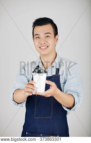 Smiling Coffeeshop Owner In Denim Apron Giving Cup Of Take Out Coffee