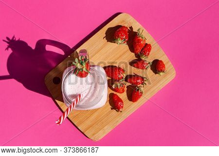 Strawberry Smoothie In A Glass Jar With A Red-striped Tube. There Are Strawberries On A Wooden Board