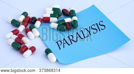 Paralysis Words On A Blue Sheet Of Paper Against The Background Of Multicolored Tablets. Medical Con