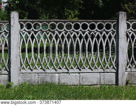 Openwork Concrete Fence Of A Green Garden
