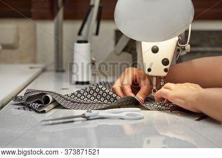 Girl Seamstress Sew On The Sewing Machine. Womens Hands Sewing On The Sewing Machine