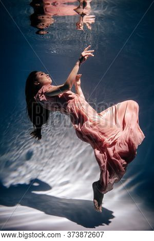 Woman Wearing Fashion Pink Dress Underwater Pool. Beautiful Young Lady Model With Long Hair And Wear