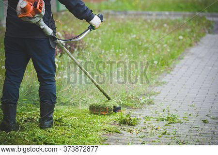 Worker In Dark Protective Clothing With A Gas Mower In His Hands, Mowing Grass In Front Of The House