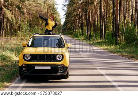Woman Sitting On Car Sunroof Summer Road Trip. Fashionable Girl In Leather Jacket, Hat And Sunglasse