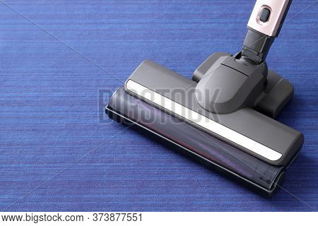 Head Of Modern Vacuum Cleaner On Blue Carpet Background. Close Up.