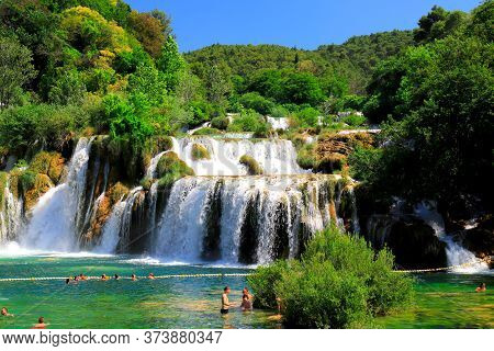 Tourists Swim In The Lake Near Picturesque Cascade Waterfall In Summer. The Best Big Beautiful Croat
