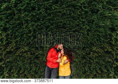 A couple in love is lying on the green grass. A beautiful couple in red and yellow jackets embrace. A happy couple embrace while lying on the grass. Lovers kiss. Love relationship. Copy space