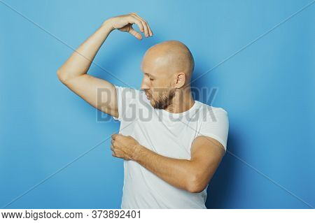 Young Man In A White T-shirt With Wet Armpits From Sweat On A Blue Background. Concept Of Excessive