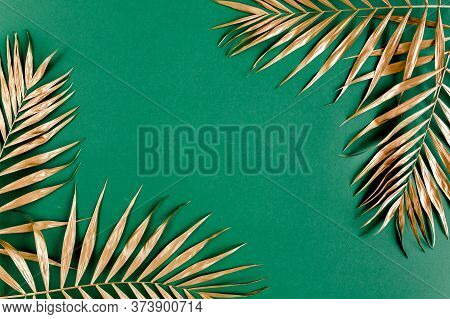 Gold Tropical Palm Leaves Monstera On Green Background. Flat Lay, Top View Minimal Concept.