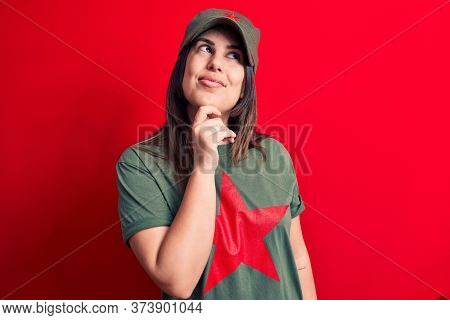 Young beautiful brunette woman wearing cap and t-shirt with red star communist symbol smiling looking confident at the camera with crossed arms and hand on chin. Thinking positive.