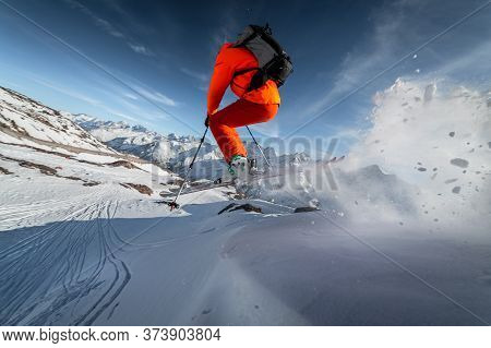 Close-up Athlete Male Skier Jumps From A Snow-covered Slope Against The Backdrop Of A Mountain Lands