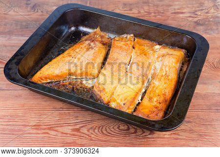 Baked Pieces Of The Trout Fillet On The Metal Oven Tray On The Rustic Table Close-up