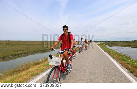 Family Cycling Pedals On The Bike Path Near Venice Island In Summer