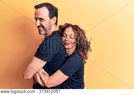 Middle age beautiful couple wearing t-shirt standing over isolated yellow background hugging oneself happy and positive, smiling confident. Self love and self care