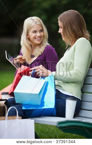 Happy young women with shopping bags using tablet PC on park bench