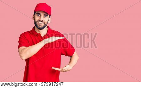 Young handsome man with beard wearing delivery uniform gesturing with hands showing big and large size sign, measure symbol. smiling looking at the camera. measuring concept.