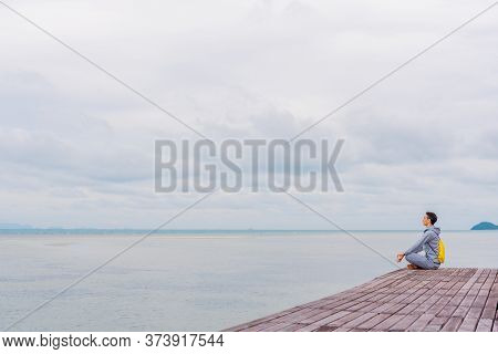 A Man In A Gray Tracksuit Sits On The Edge Of A Pier In Thailand And Practices Meditation, A Person