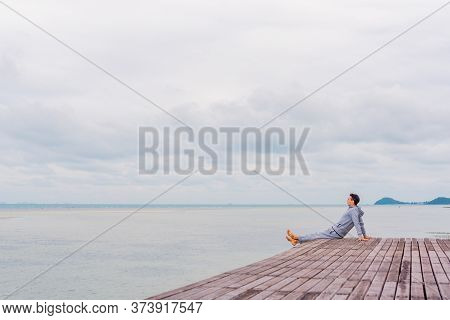 A Man In A Gray Tracksuit Rests From The Bustle Of The City On The Edge Of The Pier In Thailand, Sol