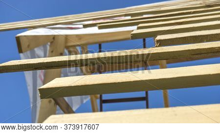 Wooden Roof With Rafter Style Framing Against A Blue Sky