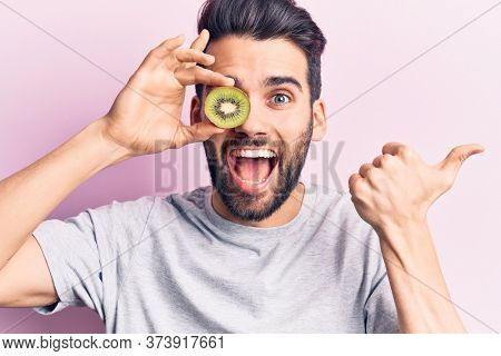 Young handsome man with beard holding kiwi over eye pointing thumb up to the side smiling happy with open mouth