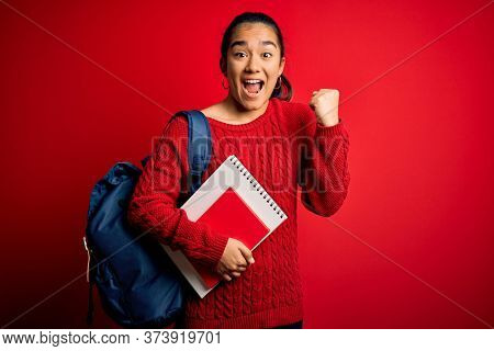Young beautiful asian student woman wearing backpack standing over isolated red background screaming proud and celebrating victory and success very excited, cheering emotion