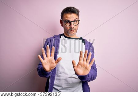 Young handsome man wearing purple sweatshirt and glasses standing over pink background Moving away hands palms showing refusal and denial with afraid and disgusting expression. Stop and forbidden.