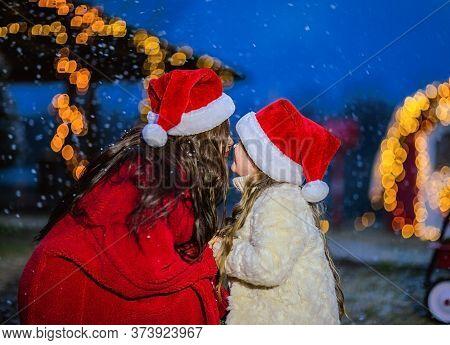 Young Brunette Woman In Red Coat And Santas Cap Kissing Young Daughter In Beige Coat And Santas Cap.