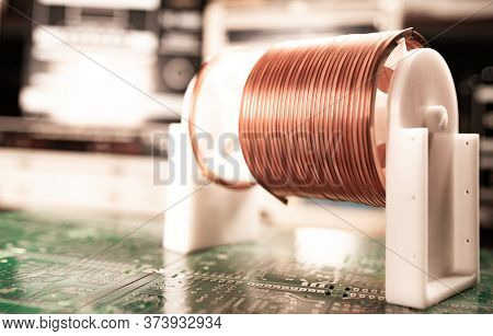 Close-up A Lot Of Skeins Of Twisted Copper Wire Are Standing On A Green Microcircuit. Factory Concep