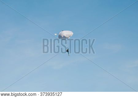 Skydiving Activity Theme. Man Gliding On White Parachute On Blue Sky Background