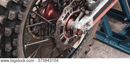 Close-up Rear Studded Wheel Of Enduro Off-road Motorcycle In Garage On Lift. Brake Discs, Chain, Tra