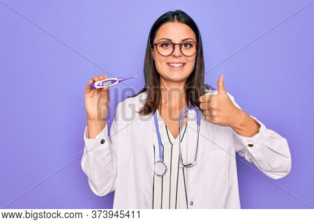 Young beautiful brunette doctor woman wearing stethoscope and coat holding thermometer Smiling happy and positive, thumb up doing excellent and approval sign