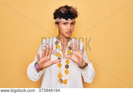 Young beautiful african american afro hippie woman wearing sunglasses and accessories Moving away hands palms showing refusal and denial with afraid and disgusting expression. Stop and forbidden.