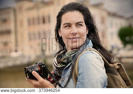 Portrait of woman reporter taking pictures with reflex camera