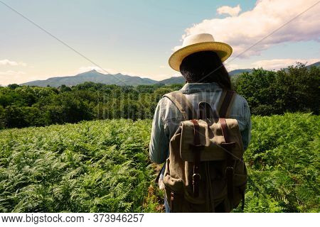 Woman with backpack on a journey in coutryside, wearing hat