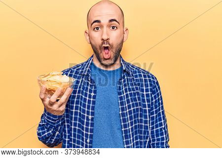 Young handsome bald man holding bowl with potato chips scared and amazed with open mouth for surprise, disbelief face