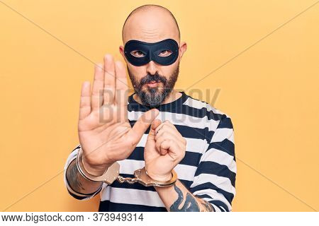 Young handsome man wearing burglar mask and handcuffs with open hand doing stop sign with serious and confident expression, defense gesture