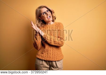 Middle age beautiful blonde woman wearing casual sweater and glasses over yellow background clapping and applauding happy and joyful, smiling proud hands together