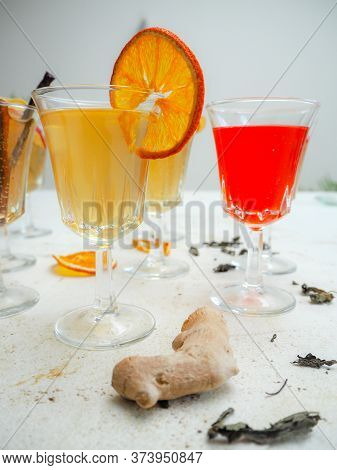 Multiple Glasses With A Variety Of Flavored Kombucha Tea Such As Citrus, Raspberry And Ginger On A W