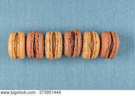 Six Coffee And Chocolated Flavoured Macaroons On Blue Vinyl Background.