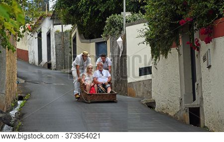 Funchal, Madeira, Portugal  -  June 26, 2019:  Funchal  Madeira  Older Couple Having Downhill  Baske