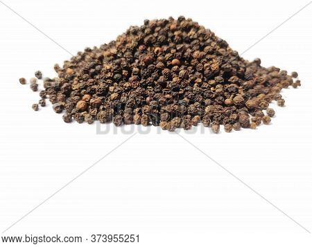 Dry Black Peppercorns Heap On White Background Sideview .